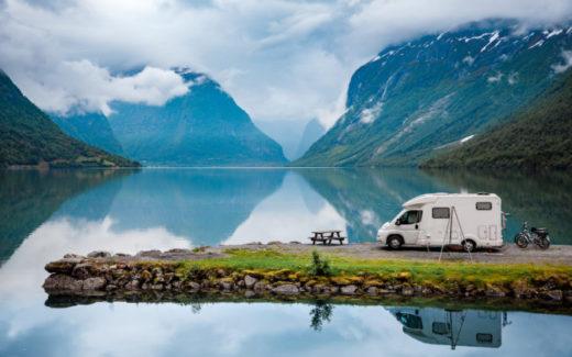 Teilintegriertes Wohnmobil auf einer Landzunge im See vor Berglandschaft