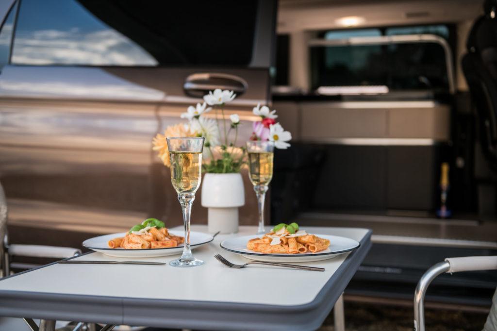 Dinner mit Pasta und Proseco vor dem Campervan Marco Polo