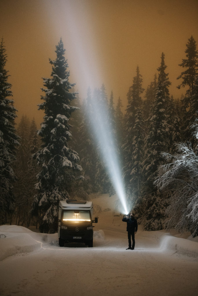 Das Bild zeigt den Allradcamper ML-T 580 im verschneiten Wald bei Nacht.